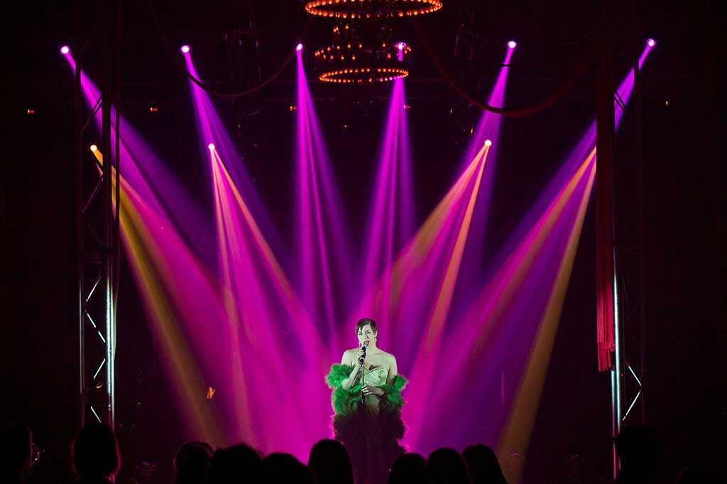 Singer performing during an event under purple lights